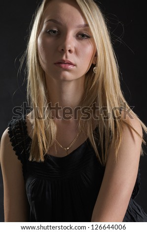 Upper body portrait of a serious young blonde woman posing in a stylish black dress against a dark background - stock photo