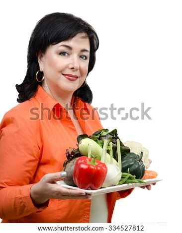 Upper body shot of mid adult woman with a tray of fresh vegetables. She is wearing a orange shirt with long sleeve