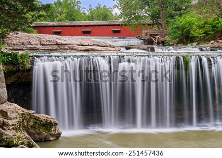 Upper Cataract Falls, a scenic waterfall in Indiana, is topped by a red historic covered bridge. - stock photo