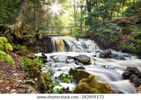Upper Chapel Falls in Spring. A sunburst appears over a flowing Upper Chapel Falls at Pictured Rocks National Lakeshore near Munising Michigan. The Pictured Rock park is in Michigan's Upper Peninsula. - stock photo