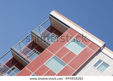 Upper corner of modern apartment condominium high rising building stretching angled into blue sky
