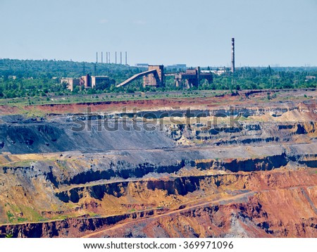 Upper levels of the iron ore open cast mine with crushing plant and pipes one the background - stock photo