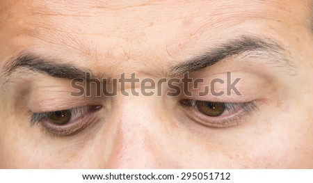 Upper part of males face closeup on eyes looking down - stock photo