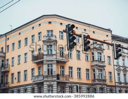 Upper Residential Apartment Floors of Urban City Corner Building with Yellow Facade and Small Balconies on Overcast Day with Gray Sky, Obscured by Traffic Street Lights Displaying Yellow Signal - stock photo