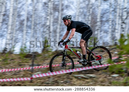 "Upper Ufaley, Russia - May 04, 2015: A mountain biker competes during the race ""Le Tour de Turshavel 2015"""