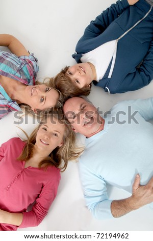 Upper view of family of 4 people laying on the floor