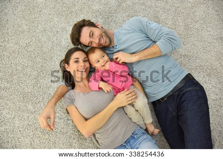 Upper view of family of three laying on carpet - stock photo