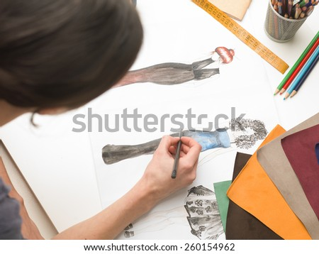 upper view of fashion designer sitting at desk, sketching in her atelier - stock photo