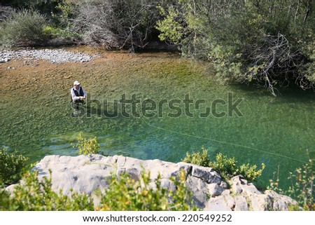 Upper view of fly fisherman fly-fishing in river - stock photo