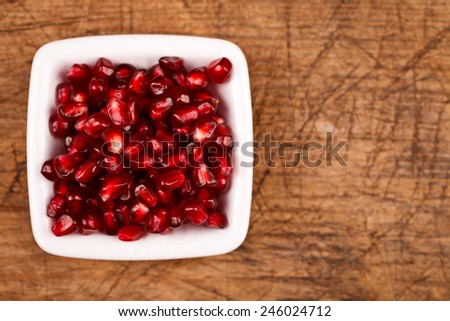 Upper view of grenadine seeds in white plate, wooden background - stock photo