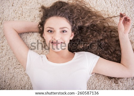 Upper view of. Smiling woman is relaxing laid on floor. Looking at camera. Close-up. - stock photo