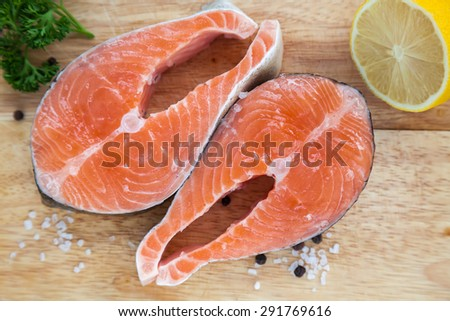 upper view of two salmon steaks on a wooden board - stock photo