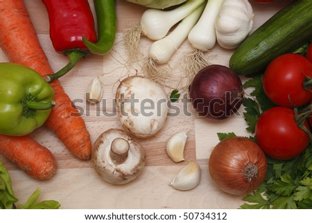 Upper view of vegetables on a wooden chopping board.