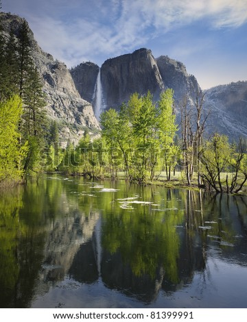 Upper Yosemite Falls reflected with floating ice in the river