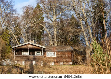 UPPSALA, SWEDEN, JANUARY 2015, a brown, traditional looking log cabin on the forest on a sunny winter day.