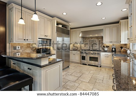 Upscale kitchen in luxury home with breakfast bar - stock photo