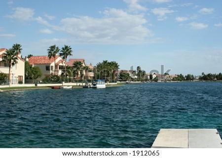 Upscale lake homes and dock - stock photo
