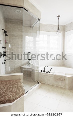 Upscale neutral-toned bathroom with jacuzzi tub and shower. Vertical format.