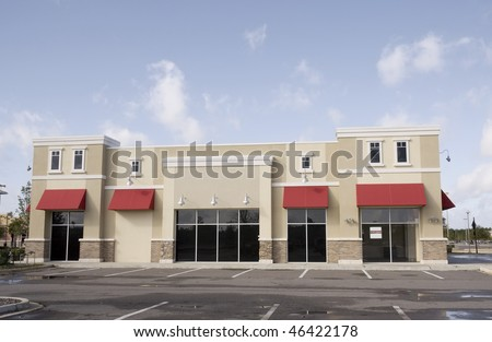 upscale pastel strip mall building with red awnings and tinted glass - stock photo