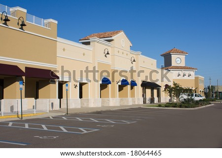 upscale pastel strip mall with awnings and corner clock tower - stock photo