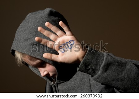 Upset abused frightened little child (boy), stop hand gesture close up horizontal dark portrait with copy space - stock photo