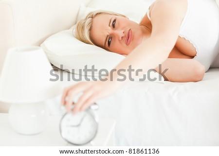 Upset blonde woman waking up in her bedroom - stock photo