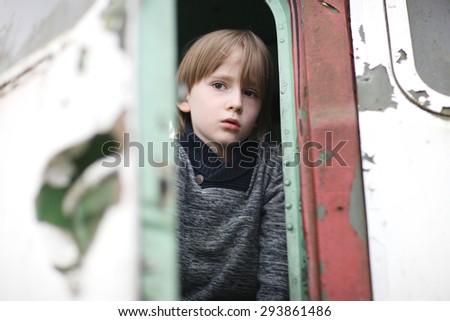 Upset boy face between the doors of an aged car - stock photo