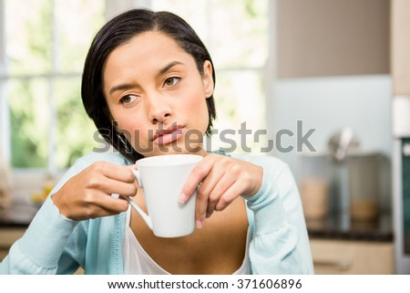 Upset brunette holding white cup in the kitchen