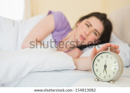 Upset brunette in her bed turning off her alarm clock - stock photo