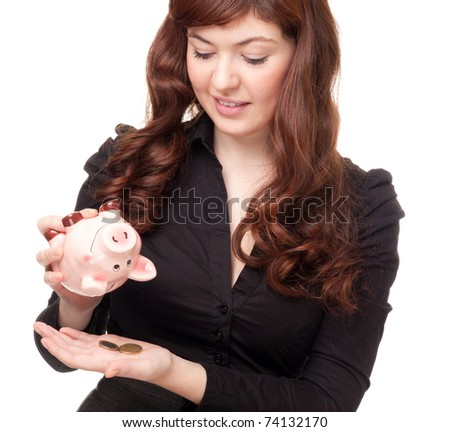 Upset business woman collecting coins from a piggy bank on white background