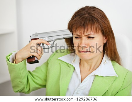 Upset business woman in green suit keeps gun near his temple on white office background - stock photo