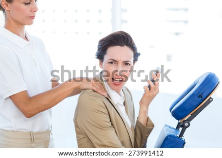 Upset businesswoman having back massage in medical office - stock photo