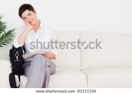 Upset Businesswoman with a paper and a bag in a waiting room - stock photo