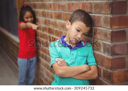 Upset child being teased by another child on the elementary school grounds - stock photo