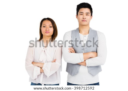 Upset couple standing with arms crossed on white background - stock photo