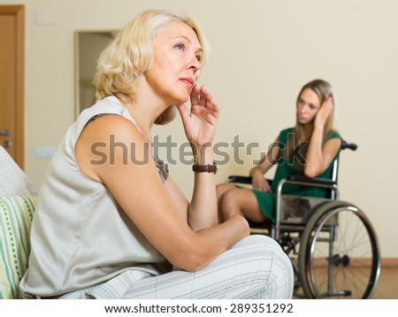 Upset elderly woman and handicapped girl having domestic quarrel - stock photo