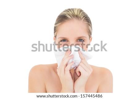 Upset fresh blonde woman sneezing in a tissue on white background - stock photo