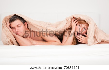 Upset frustrated and bored couple lying in bed having no sex - stock photo