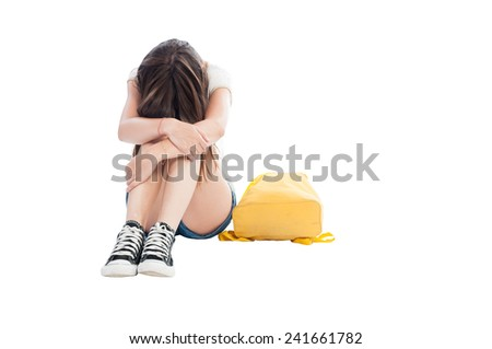 Upset girl holding her head on knees on white background - stock photo