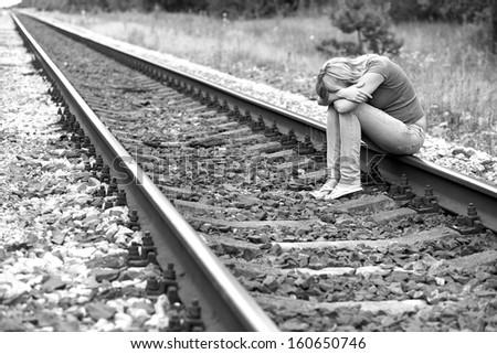 upset girl sitting on the rails - stock photo