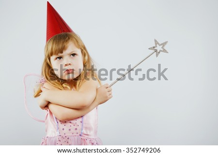 Upset girl, with curly blond hair, wearing on pink dress, red festal hat and fairy wings on her back, posing with silver magic stick, on white background, in studio, waist up - stock photo