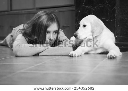 Upset girl with her friend, golden retriever. Monochrome photo