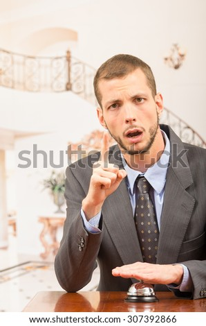Upset guest businessman customer ringing hotel bell in reception desk demanding attention close up - stock photo