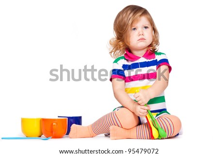 Upset little girl play with dishes - stock photo