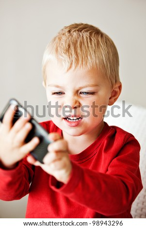 upset little 3 year old boy is frustrated with the media player or electronic toy he is holding - stock photo