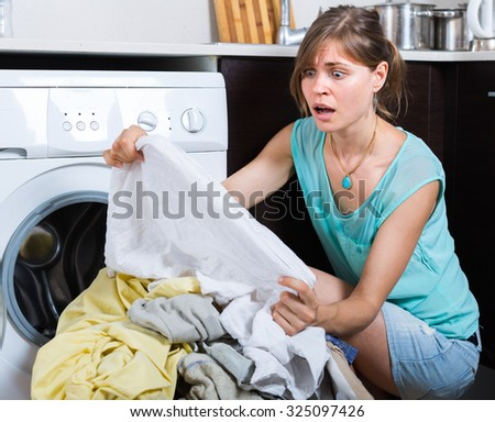 Upset maid looking at clothes with persistent stains after laundry - stock photo
