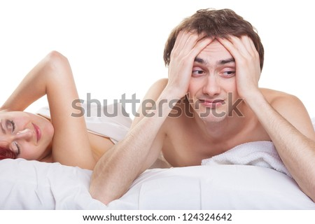 Upset man having problem on the bed with his wife on white background - stock photo