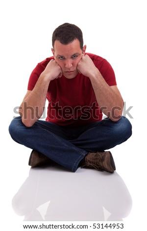 upset man sitting cross-legged on the floor, isolated  on white background. studio shot - stock photo