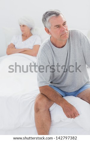 Upset man sitting on bed during a dispute with wife with arms crossed