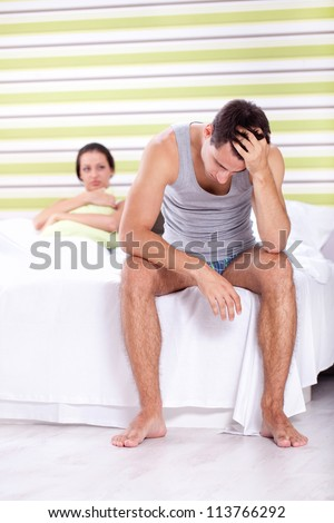 Upset men sitting on bed with his wife in background, relationship trouble - stock photo